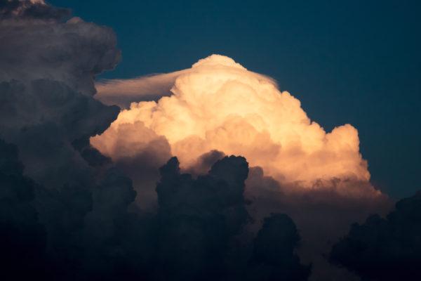 bild einer vom licht erhellten Wolke, die sich durch eine dunkle Wand kämpft